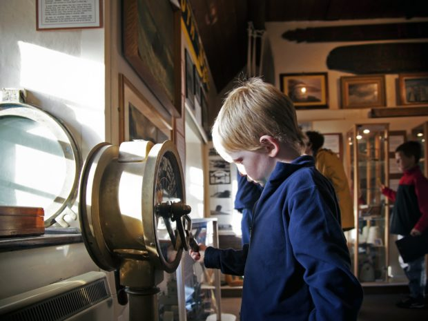 Child turning a lever on a museum object