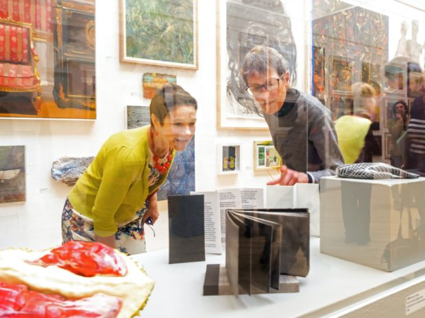 Woman and man look at object inside an exhibition glass case
