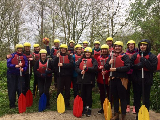 16 people wearing helmets, life jackets and