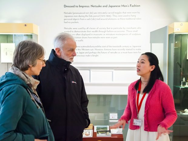 Two museum visitors listen to a museum volunteer speak.