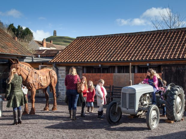 Some children sit on a tractor, some stand next to the tractor. An adult female looks at an exhibit of a horse. Farm buildings and Glastonbury Tor form a backdrop to the image