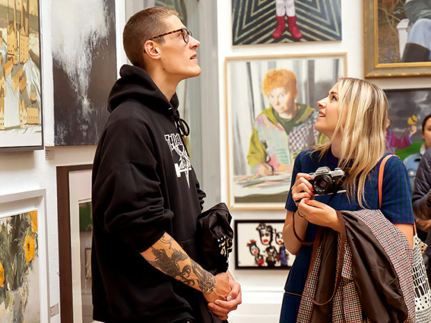 Two young adults look at paintings