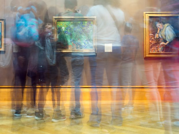 A long exposure of multiple visitors at a gallery